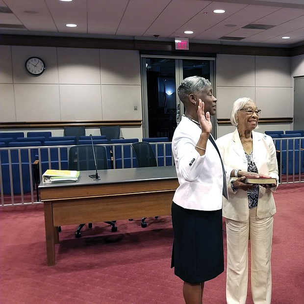 Colette W. McEachin is sworn in as Richmond's new commonwealth's attorney Tuesday morning by Judge Joi Jeter Taylor, chief judge of the Richmond Circuit Court, as Mrs. McEachin's proud mother, Gladys Wallace, holds the Bible. Mrs. McEachin's husband, Congressman A. Donald McEachin of Richmond, Richmond Circuit Court Clerk Edward F. Jewett and several of Mrs. McEachin's deputy commonwealth's attorneys also attended the ceremony at the John Marshall Courts Building in Downtown. Mrs. McEachin, who has more than 20 years of experience as a city prosecutor, took over the top job after veteran Commonwealth's Attorney Michael N. Herring left July 1 to become a partner in the McGuireWoods law firm. Mr. Herring, who recommended Mrs. McEachin for the top post, is backing her in the Nov. 5 special election when voters will formally choose his successor.