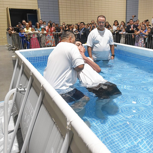 """Attendants perform one of several baptisms last Saturday during the Jehovah's Witnesses regional convention at the Greater Richmond Convention Center. Thousands of people from Virginia and nearby states attend the denomination's series of three-day conventions each summer in Downtown. This year's theme: """"Love Never Fails!"""" Highlights include symposia, song, prayer, films and dramatic Bible readings around the theme. The next gathering in the series will be this Friday through Sunday at the convention center. (Clement Britt)"""