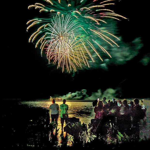 Spectators enjoy fireworks over the Appomattox River from the beach at Hopewell's City Park last Saturday. It was the first of several holiday fireworks displays in the area. (James Haskins/Richmond Free Press)
