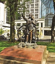 A bronze monument in downtown's Portland's Chapman Square installed in 1993 commemorates the 150th anniversary of the Oregon Trail by depicting a white pioneer family - father, mother, and son - at the end of their journey. Author Cynthia Culver Prescott says it also enshrines white cultural superiority as well as gender stereotypes.