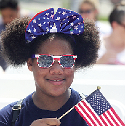 Star-Spangled Celebration A youngster with Deborah De Los Santos' summer camp group waves Old Glory at the Fourth of July ceremony to swear in new U.S. citizens at the Virginia Museum of History & Culture on Richmond's Arthur Ashe Boulevard. (Regina H. Boone/Richmond Free Press)