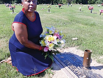 Adeline U. Clarke kneels beside the recently installed marker at her parents' gravesite in Forest Lawn Cemetery in Henrico County. She finished paying for the marker in November, but had to badger the cemetery for months before it was installed.