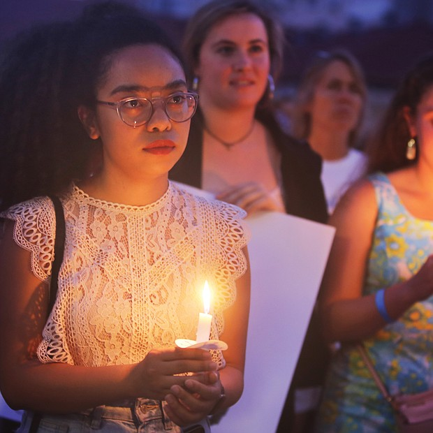 "Adele McClure, left, holds a candle during last Friday's ""Lights for Liberty"" vigil on the State Capitol grounds calling for an end to the detention camps and family separations imposed on migrants to the United States along the southern border. Hundreds of people attended the vigil, which was sponsored by numerous Richmond area organizations, including Indivisible Virginia, the Virginia ACLU, UndocuRams and ReEstablish Richmond. Local activists, advocates and others spoke at the event, which was one of nearly 700 Lights for Liberty events held around the globe. (Regina H. Boone/Richmond Free Press)"