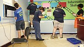 A team of Capital One volunteers from Richmond, Northern Virginia, Maryland, Delaware, New Jersey, New York, New Orleans and Texas put a fresh coat of paint on a new office for the principal at Fairfield Court Elementary School on Wednesday as a part of RPS Shines 2019.