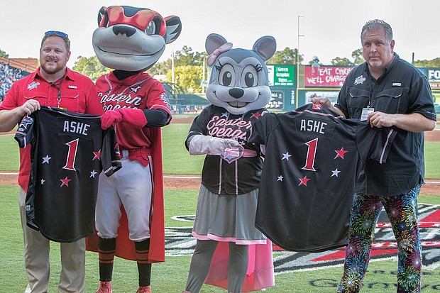 """The late Richmond native and tennis great Arthur Ashe Jr. is remembered and honored with jerseys bearing his name during the All-Star Game at the baseball stadium located on Richmond's Arthur Ashe Boulevard. Showing the jerseys to the crowd are, from left, Ben Rothrock, the Squirrels' general manager; team mascots Nutzy and Nutasha; and Todd """"Parney"""" Parnell, the Squirrels' vice president and chief operating officer."""