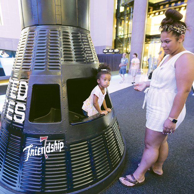 Out of this world/  Harper Miller peers out from her perch in a replica of Friendship 7, the Mercury capsule in which astronaut John H. Glenn Jr. became the first American to orbit the Earth in February 1962. The youngster was visiting the Science Museum of Virginia with her mom, Kali Miller, and other family members last Saturday as part of the 50th anniversary celebration of the Apollo 11 landing on the moon.