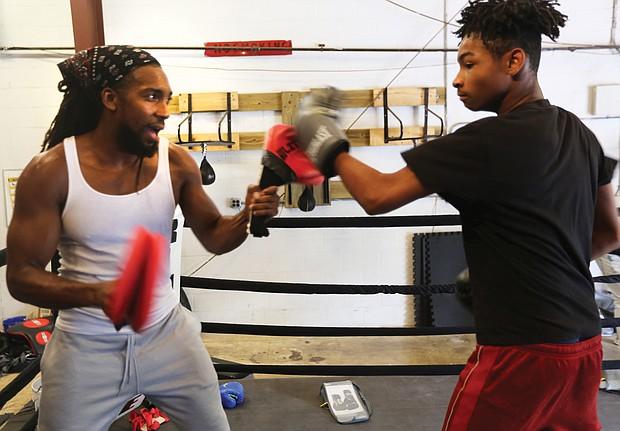 Cherry Pick'd Boxing/ Coach and trainer Tony Cherry, left, helps Deon Jones, 13, hone his skills at Cherry Pick'd Boxing. (Regina H. Boone/Richmond Free Press)