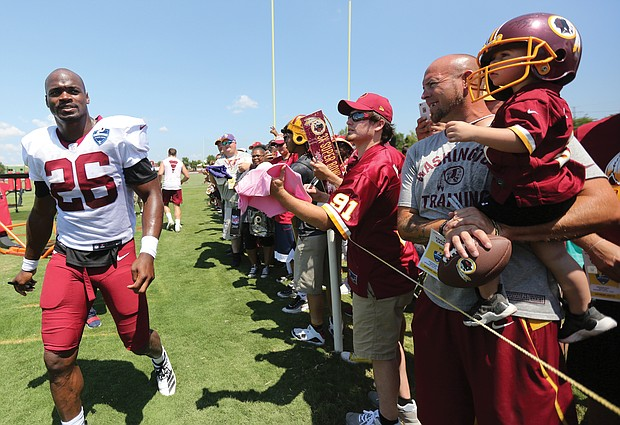 Adrian Peterson, a star running back for the Washington NFL team, strides past fans after a practice session.