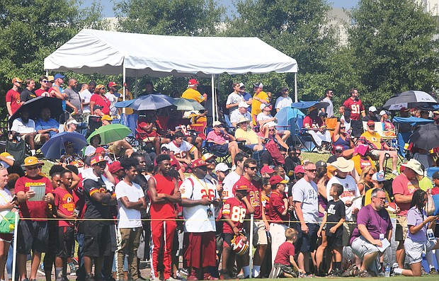 Hundreds of fans watch the Washington NFL team's training session on Saturday. The training camp will continue, and be open to fans, through Aug. 11.