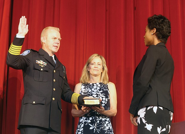 """Richmond Police Chief Will Smith is sworn in as the city's top cop during a ceremony Wednesday held at Virginia Union University's Coburn Hall. The chief's wife, Virginia """"Ginnie"""" Smith, holds the Bible while City Clerk Candice Reid administers the oath. Chief Smith is the city's 19th police chief. He was joined at the ceremony by his two daughters, Mayor Levar M. Stoney, members of City Council and dozens of current and retired law enforcement officers from Richmond and around the state. (Regina H. Boone/Richmond Free Press)"""