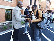 Dontrese Brown, vice chair of the board of directors of Cristo Rey Richmond High School, greets freshman Joshua in a welcome line set up by board members and staff on the first day.