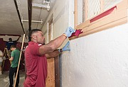 Washington running back Chris Thompson paints at Carver Elementary School during the team's project to spruce up the laundry area. The project took place last month while the team was in Richmond at its preseason training camp.