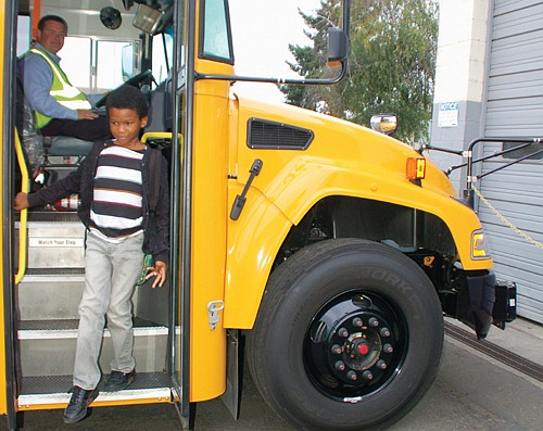 Jaheim Adrien, 7, of Portland demonstrates a safety best practice by exiting the school bus while using a handrail.