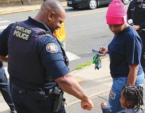Sgt. Israel Hill of the Portland Police Bureau's North Precinct gets a fist bump hello from a young resident on his way to school.