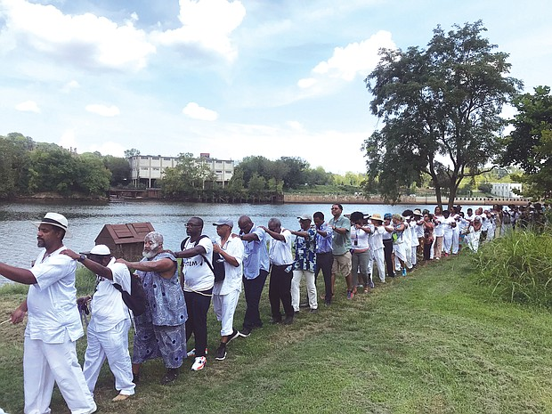 A line of people marches along a portion of the Richmond Slave Trail beside the James River on their way from the Old Manchester docks to Downtown. The walk on Aug. 20 was led by Janine Y. Bell of the Elegba Folklore Society and was symbolic of the many slave coffles in Richmond, which was one of the largest markets for the sale of enslaved people before the end of the Civil War. The walk was one element of the three-day Black Lives Global Summit that the Connecticut-based Community Healing Network sponsored. The summit, held largely at Virginia Union University in concert with other events related to the 400th anniversary of the forced arrival of the first Africans in English North America, focused on providing emotional and psychological healing from the lingering impact of slavery and included a range of speakers focusing on the past, present and future for people of African descent. (Regina H. Boone/Richmond Free Press)