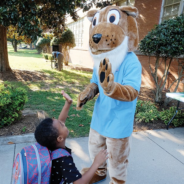 Nehemiah Wright, 5, high fives the cougar mascot at John B. Cary Elementary School as he arrives Tuesday, eager to get the new school year started.