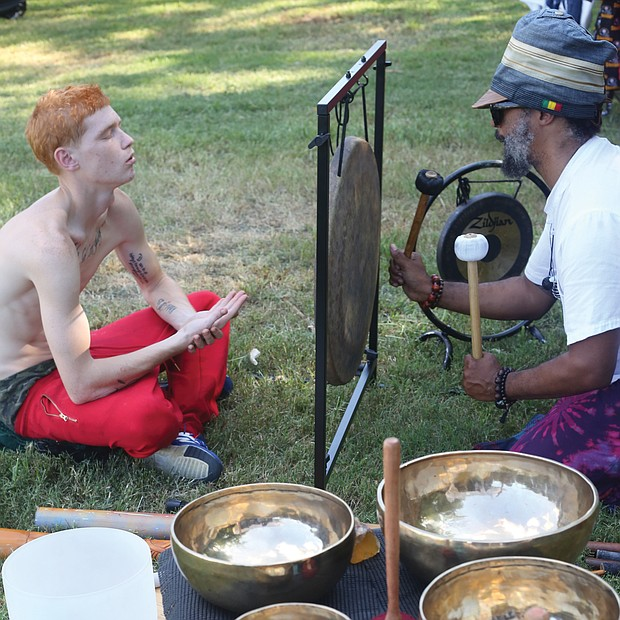 Julian Desta, right, leads an individual sound healing bath session for Russell Gray. It was Mr. Gray's first time undergoing the healing.