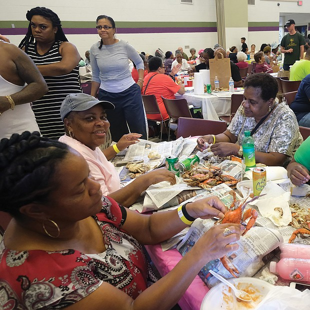 A real feast/ Hundreds of people are in crab heaven at the all-you-can-eat Crab Feast & Fish Fry held last Saturday by the Men of St. Peter's Episcopal Church at Peter Paul Development Center in the East End. The annual event benefits the outreach and community center that serves seniors and after-school programs for youngsters. Enjoying the meat they picked from crabs are, seated clockwise from left, Rhonda Thorpe, Delores Key, Catherine Rob- inson and Nicole Robinson. (Sandra Sellars/Richmond Free Press)