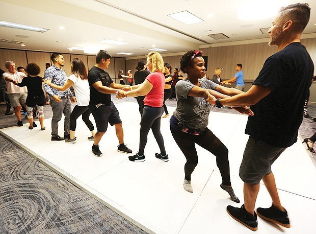 No do-si-do here/Participants watched them demonstrate central bachata, then practiced the moves as they rotated partners. At far right, Nikkia Parker of Richmond and Noel Aguilar of Williamsburg share a dance as they practice moves during a workshop last Saturday. (Regina H. Boone/Richmond Free Press)