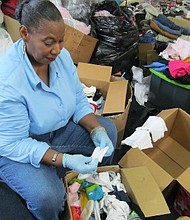 Volunteer sorting through baby clothing at collection and distribution center