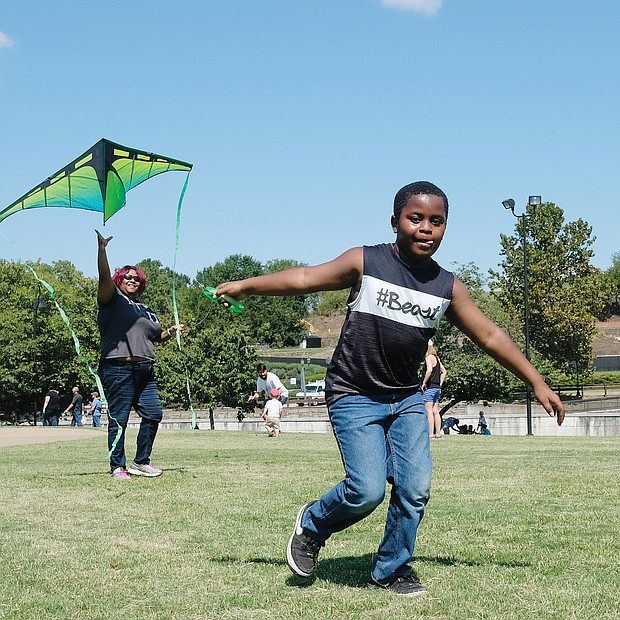 High flier! Kyan Nixon, 9, races to head off a hard landing by the kite launched by his mother, Jess Nixon, during the low winds last Saturday at the World Heritage Festival and Festival of Kites on Brown's Island in Downtown. The waterfront festival drew kite fliers, a variety of artists and vendors offering wares and representatives of nonprofit and other organizations offering information. (Sandra Sellars/Richmond Free Press)