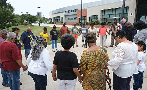 Area ministers and church members gather last Saturday outside Martin Luther King Jr. Middle School in the East End to ...