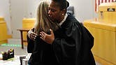 At the trial's end, Dallas District Judge Tammy Kemp leaves the bench and hugs Ms. Guyger before the former officer is taken away to begin serving a 10-year sentence for Botham Jean's murder.