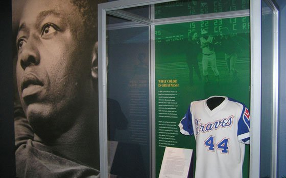 "Hank Aaron became one of the most notable figures in baseball by breaking Babe Ruth's home run record. The Museum of Science exhibit ""Baseball as America"" highlights this and discusses the opposition Aaron faced as a black baseball player."