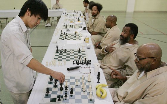 Princeton University student David Wang makes a move as he plays chess with inmate Kelvin Washington (right) at...