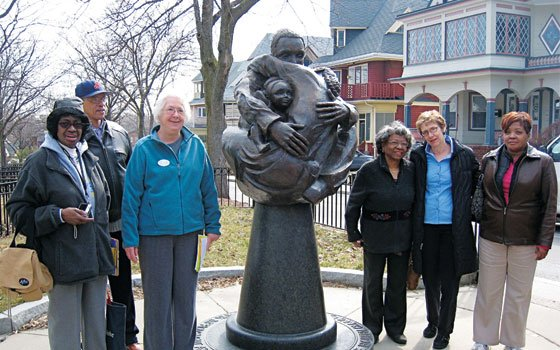 "Guides and participants on the sold-out Roxbury Women's History tour stand around Fern Cunningham's ""Family Circle"" sculpture in..."