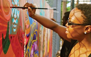 Destiny Palmer, of the Traditions Remixed artist collective, adds a final touch...