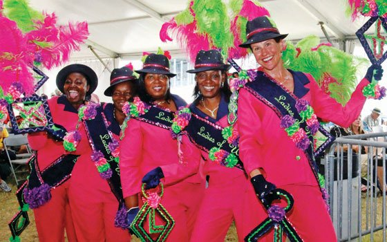The Ladies of Unity Social Aid and Pleasure Club stop to pose for fans as they dance around...