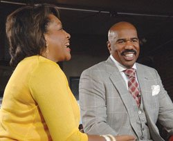 """Comedian and best-selling author Steve Harvey visited Boston to promote his new daytime television show, premiering on WCVB Channel 5 at 10 a.m. on September 4. Harvey posed with (L-R): Darryl Settles, owner of Darryl's Corner Bar and Kitchen, where the special VIP taping took place, """"CityLine"""" Host Karen Holmes Ward and WCVB-TV General Manager Bill Fine."""