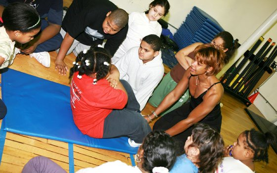 Brandy Cruthird (right) holds a young girl's feet as she performs a sit-up as a group of youngsters...