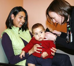 Whittier Street Health Center Pediatric Nurse Practitioner, Julianne Walsh, provides a check-up for an infant.