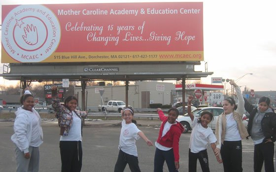 A group of students pose in front of the Mother Caroline Academy and Educational Center billboard, originally placed...