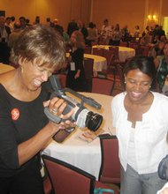WBZ-TV broadcaster Liz Walker (left) interviews Giovanna Negretti of ¿Oíste? (right) with a handheld digital camera as state Rep. Linda Dorcena Forry (center), a first-time convention delegate, looks on.