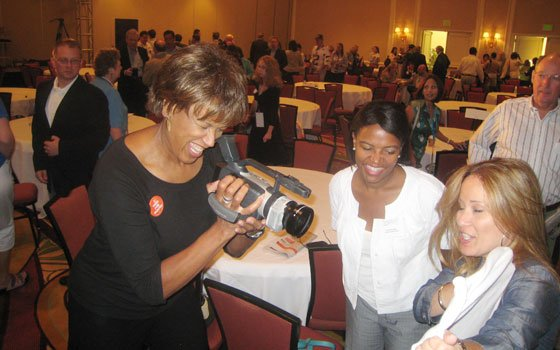 WBZ-TV broadcaster Liz Walker (left) interviews Giovanna Negretti of ¿Oíste? (right) with a handheld digital camera as state...