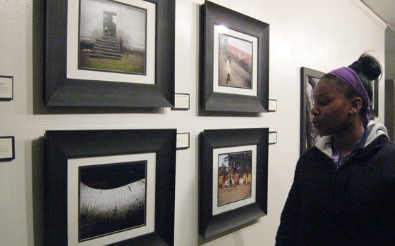 A young visitor looks at a display of photographs created by teens in Peace in Focus workshops. The...