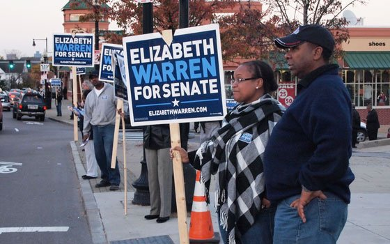 Warren campaign Senior Advisor Steve Tompkins (R) lends a hand during a standout on Blue Hill...