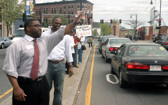 Egobudike Ezedi (left) greets motorists on Blue Hill Avenue in Grove Hall during a campaign kickoff event held...
