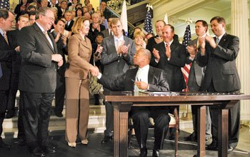 Gov. Deval Patrick shakes Senate President Therese Murray's hand after signing...