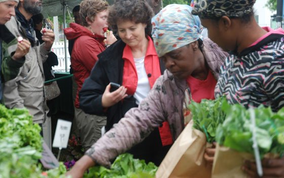 A woman purchases fresh locally grown produce at a new farm stand on Blue Hill Avenue in Dorchester. The...