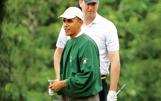 President Barack Obama pauses while playing golf with White House Trip Director Marvin Nicholson at the Vineyard Golf...