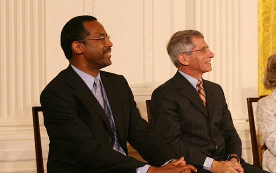 Dr. Benjamin Carson (l), seated with Dr. Anthony S. Fauci, listens Thursday, June 19, 2008, as he is announced...