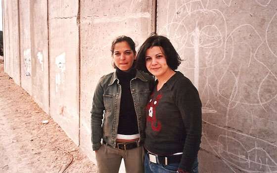Gal of Israel (l) and Rezan of Palestine (r) pose for a picture while visiting the wall that separates the...