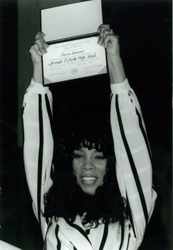 Donna Summer holds up her honorary high school diploma...