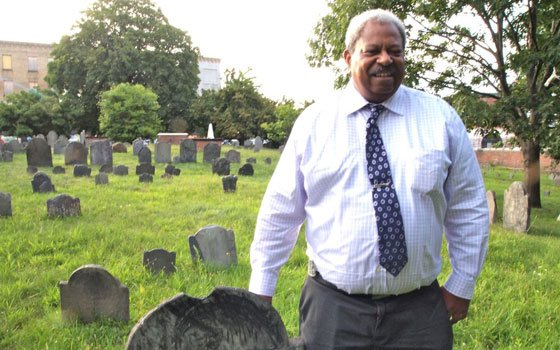 Roxbury Highlands Historical Society President Thomas Plant examines colonial history in the Eliot Burying Ground. HBI,...