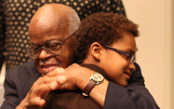 "Keith Cassim Elam, son of the late legendary hip hop artist Keith ""Guru"" Elam, is shown here hugging his grandfather Judge Harry J. Elam Sr. during a memorial service held two years ago at UMass Boston. Judge Elam passed away last week after an extraordinary legal career and legacy of social activism."