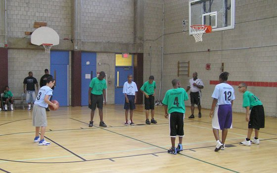 A member of the blue team prepares to shoot a free throw during a recent youth basketball game at the Hennigan Community Center in Jamaica Plain. Thanks to the efforts of Robert White, Hennigan's athletic director, neighborhood kids ages 12 and under have something positive to do during the waning weeks of summer.